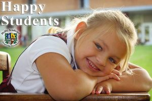 Happy Students - girl sitting at a desk